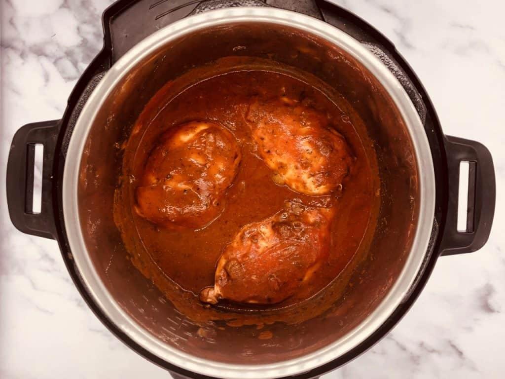 adding passata and chicken stock to Chicken Tikka Masala