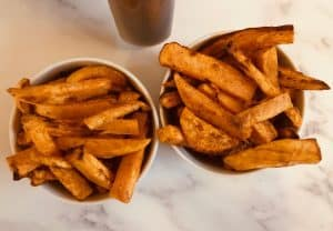 sweet potato fries in two bowls next to an air fryer
