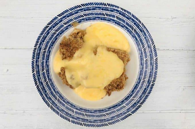 apple crumble in bowl with custard