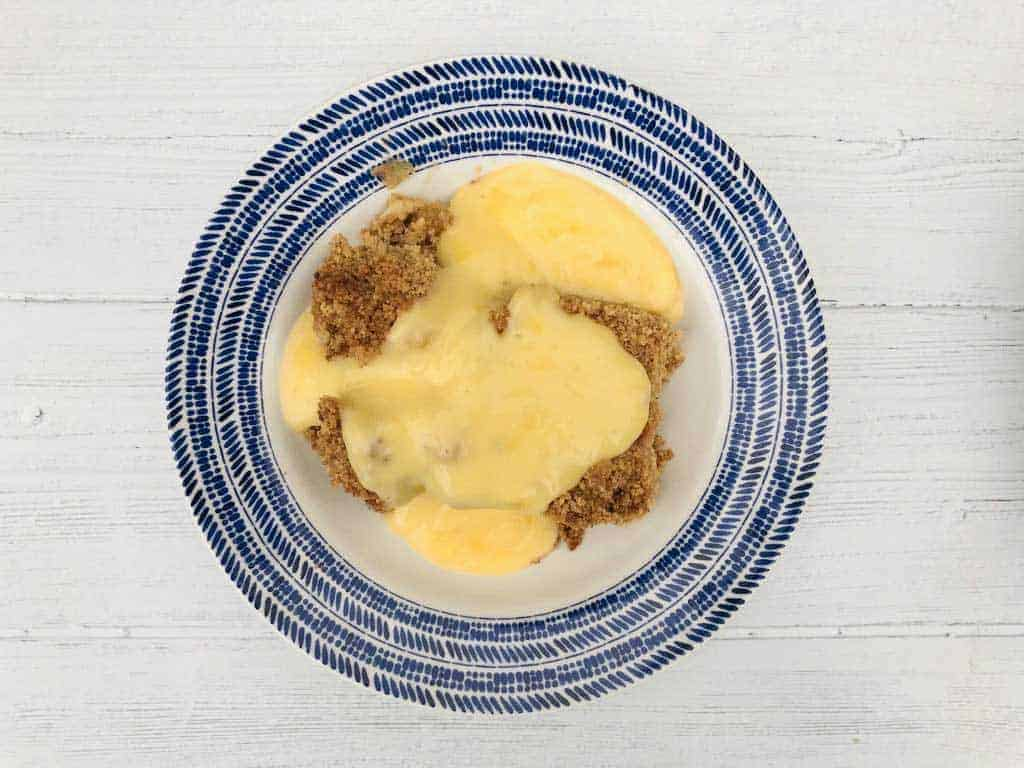 apple crumble in bowl with custard
