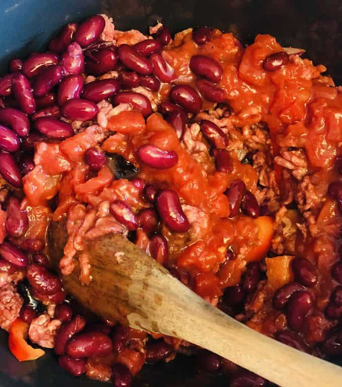 stirring ingredients for slow cooker chilli con carne