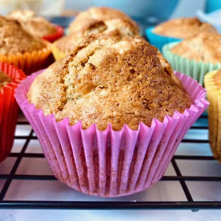 close up of banana muffin in pink case among other muffins