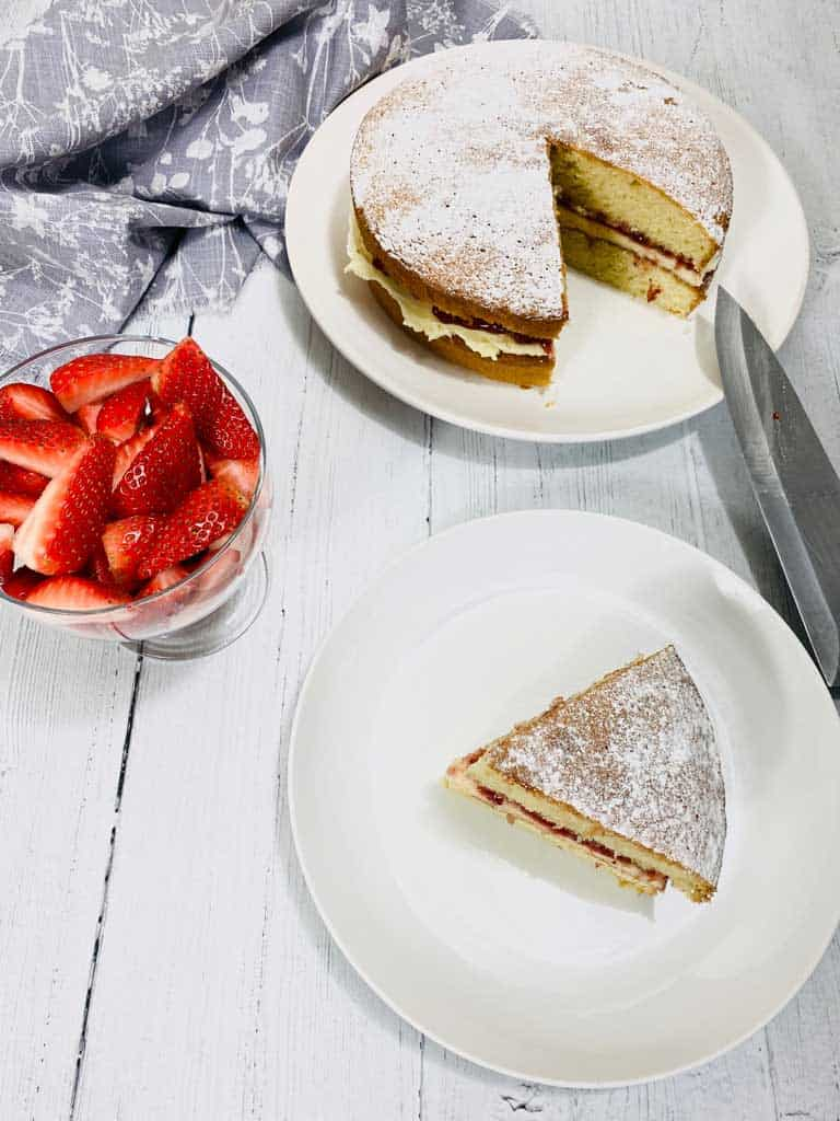 victoria sponge cake slice with cake in the background and sliced strawberries