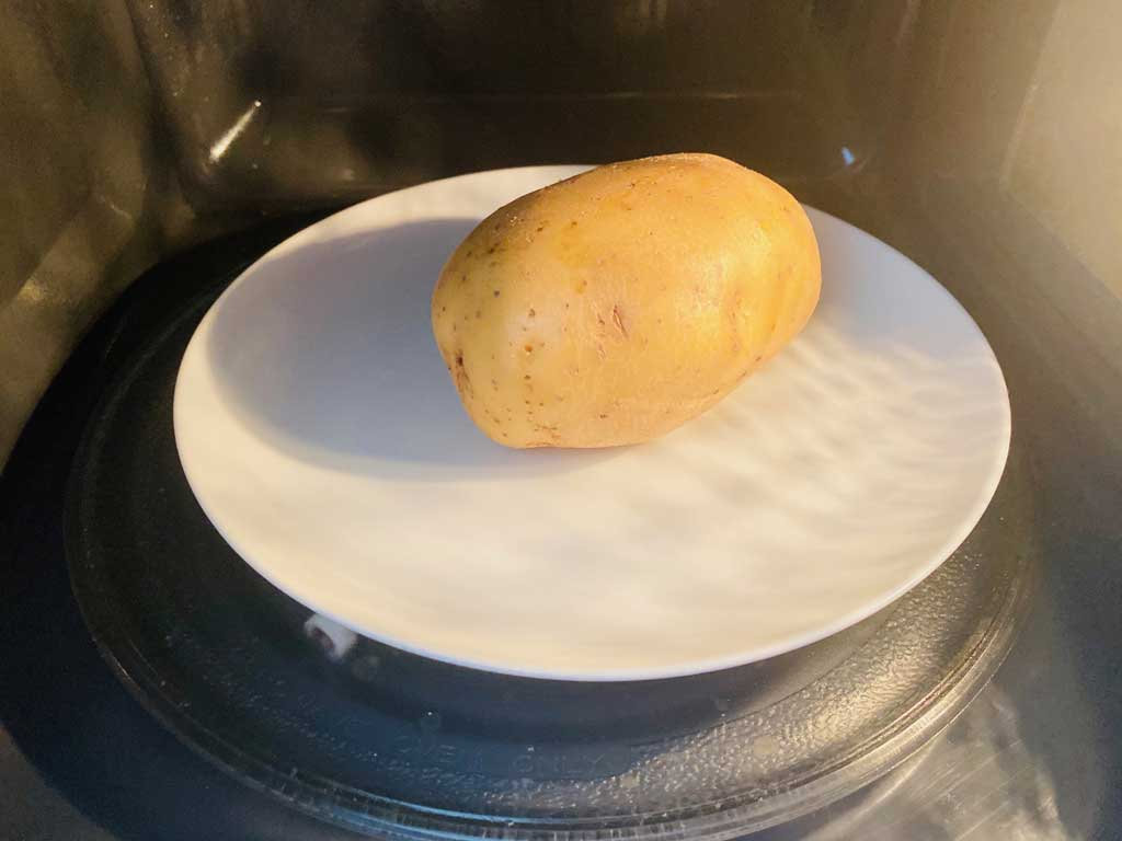potato on plate in microwave ready to cook