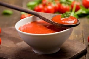 tomato passata in a bowl with a wooden spoon on top with herbs