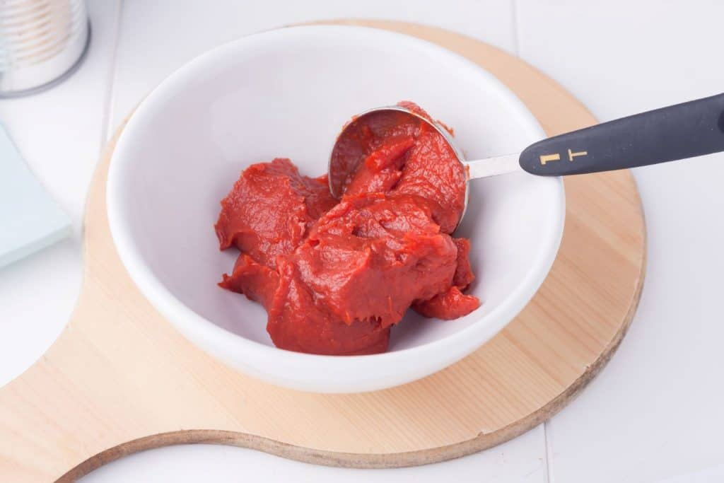 tomato puree in a white bowl on a wooden chopping board